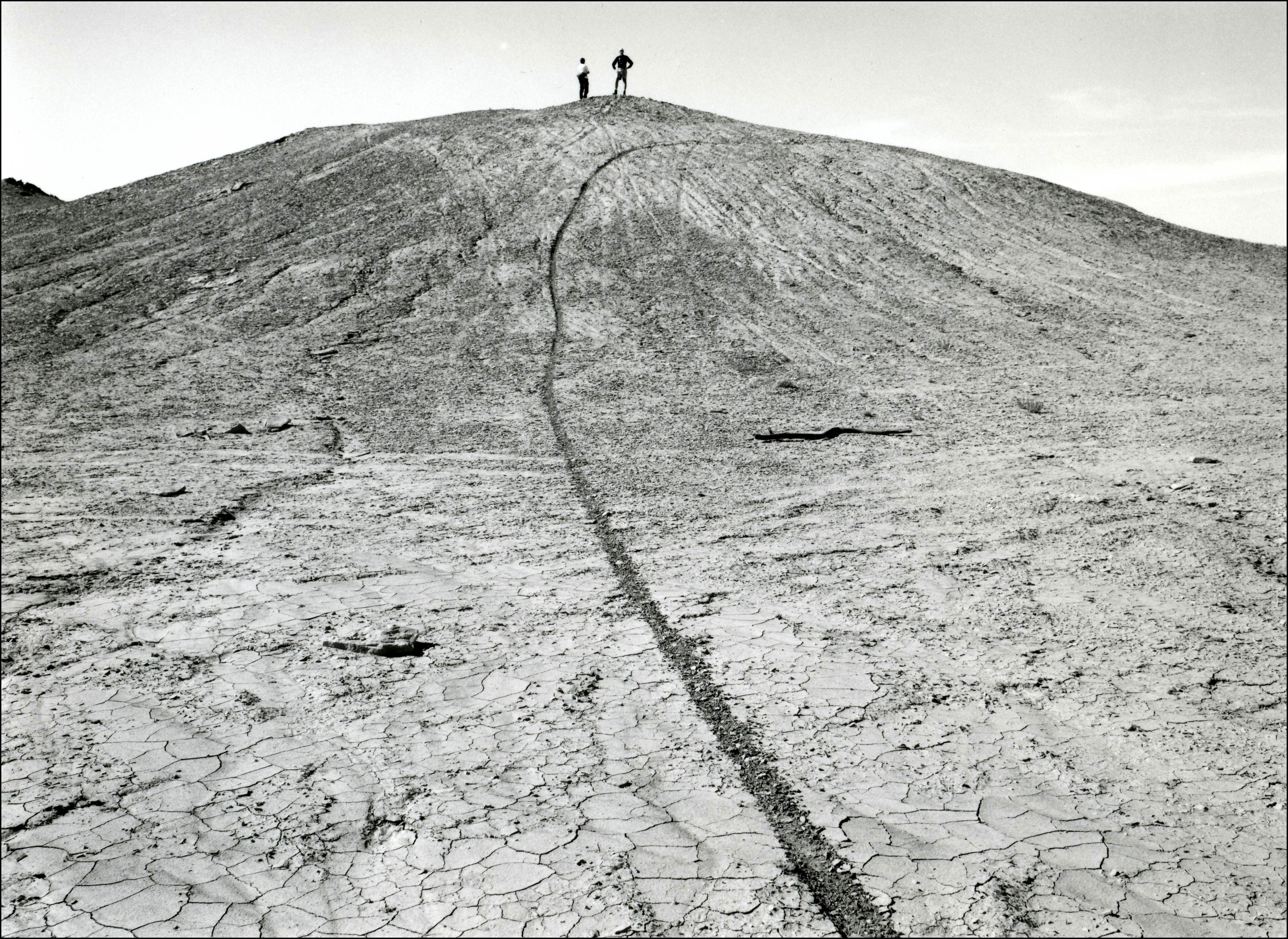 Two people standing on top of a hill in an area with cracked dirt and no vegetation. There is a single dirt bike track going up the hill.