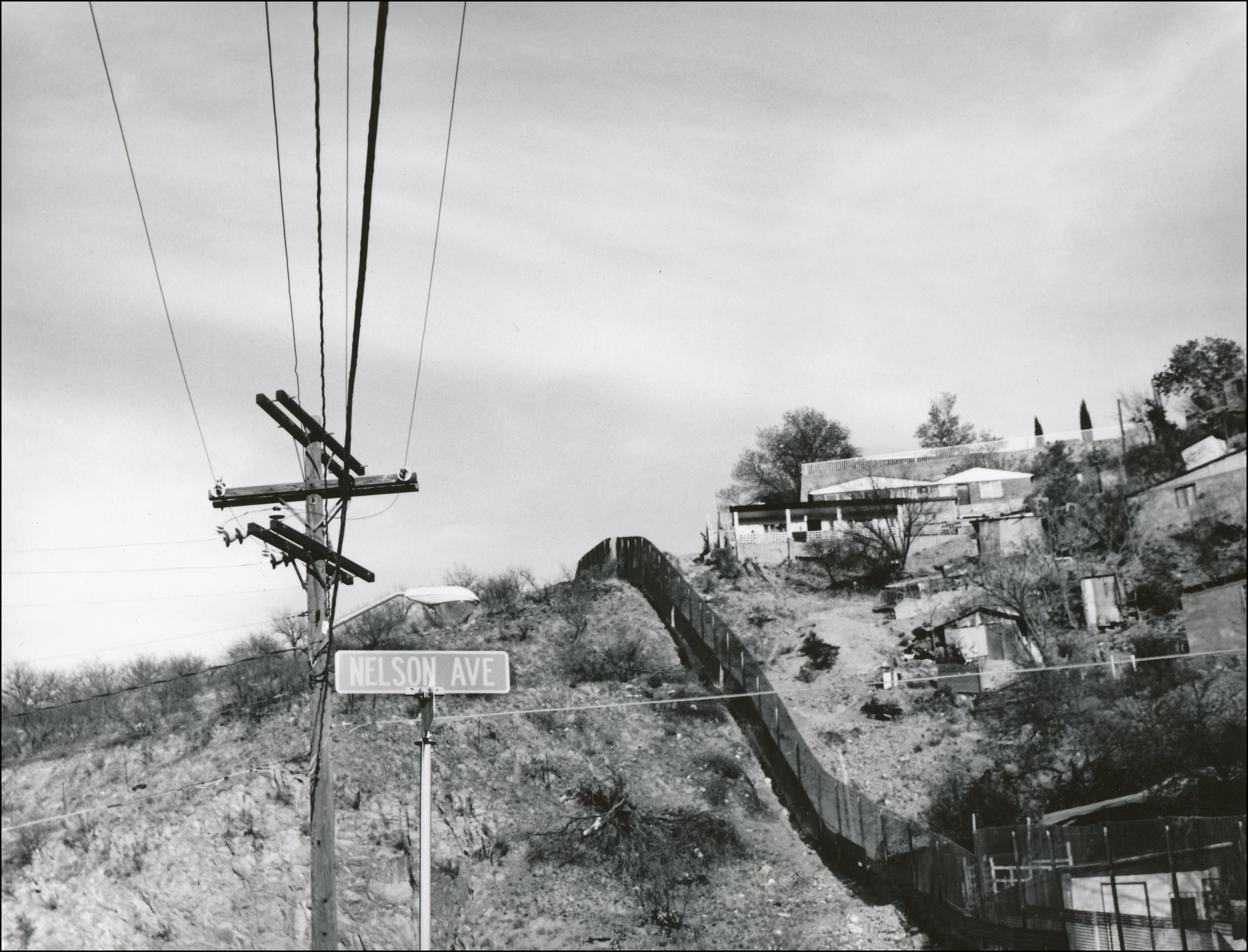 View of a border fence along a hills. Houses on right side and vegetation on left side. Also view of power lines and street sign that says Nelson Ave